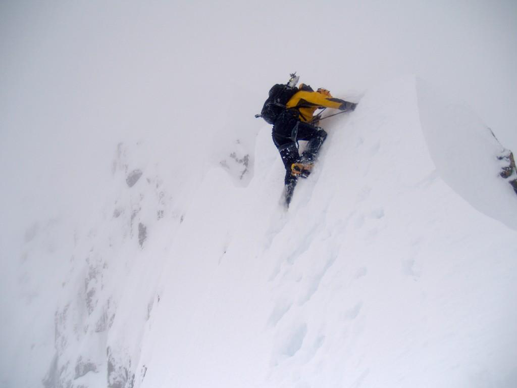 Hamish climbing over a cornice